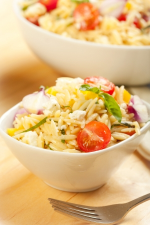 Rice like pasta orzo in a salad with basil, tomato, feta, and onion Stock Photo