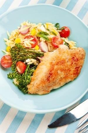 Pechuga de pollo con ensalada de pasta orzo y broccolini asado Foto de archivo - 9493578