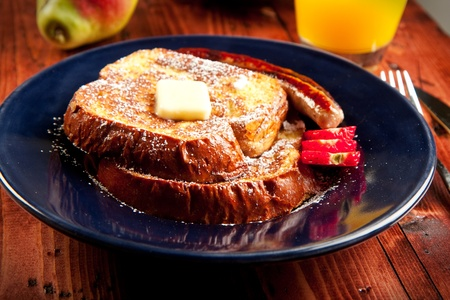Sausage accompanies French toast in a delicious breakfast photo