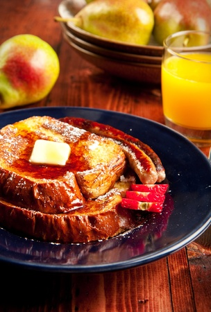 Sausage accompanies French toast in a delicious breakfast