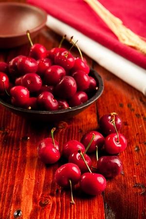 fresh juicy cherries in a rustic bowl. Focus on foreground cherries.