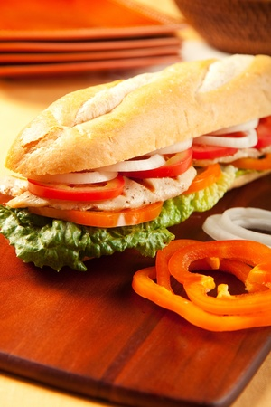 Grilled chicken sandwich with orange pepeprs, tomato, lettuce and onions