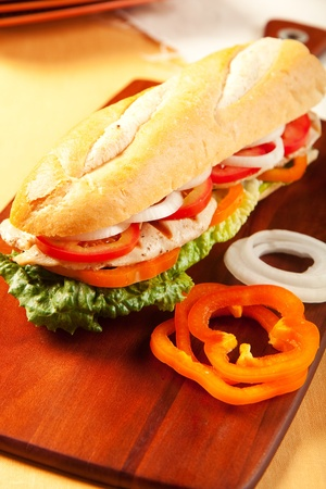 Grilled chicken sandwich with orange pepeprs, tomato, lettuce and onions photo