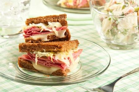 reuben: Traditional reuben sandwich cut into quarters served with potato salad Stock Photo