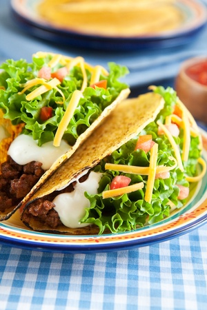 Deluxe hard shelled beef tacos served with salsa photo