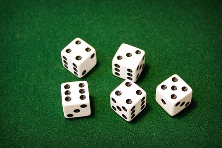 5 white dice sitting on green felt. Stock Photo