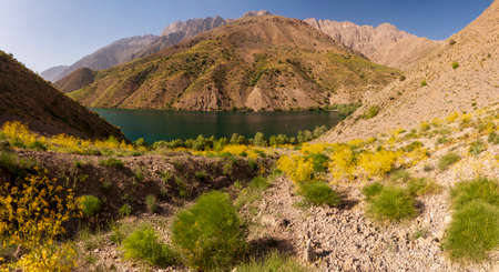 Mountain lake among rocky hills with wild green and yellow bushes near Gahar, Iran
