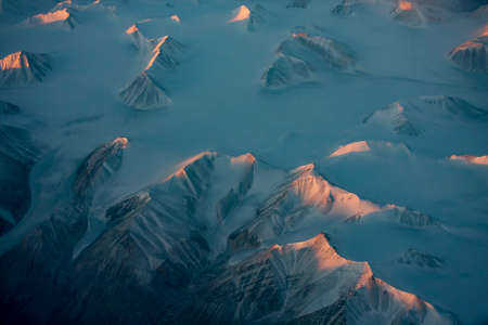 Aerial view of snowy mountain peaks of Greenland during sunset