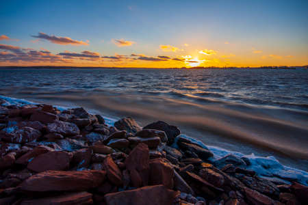 Winter landscape of a low sunset over choppy sea waters and a snowy rocky beach of Charlottetown, Prince Edward Island, Canada Foto de archivo