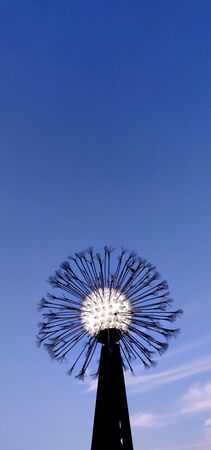 An abstract lamp that looks like a dandelion against the backdrop of a blue evening sky. 版權商用圖片