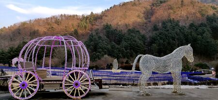 A cinderella fairy pumpkin horse cart fitted with LED lights again backdrop of beautiful mountains and glorious evening sun in garden of morning calm in South Korea.