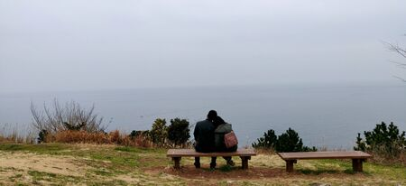 An Indian couple sitting with woman's head on man's shoulders at a bench on cliff onlooking at the vast ocean and sky during winters in jeju island, South Korea