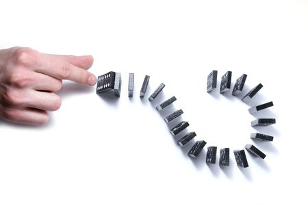chain reaction: Chain reaction dominoe que with hand isolated on white                Stock Photo