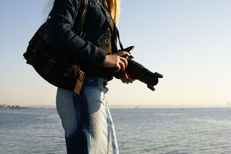 Young attractive female photographer on a beach                  photo