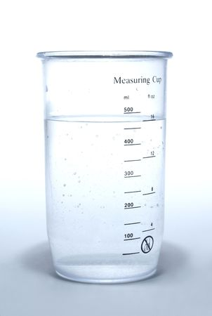 Measuring cup with liquid on white  background       Banco de Imagens
