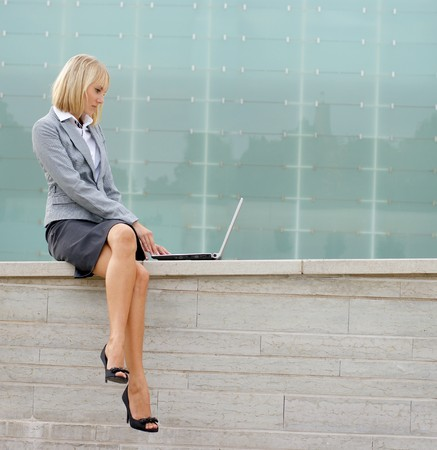 A young blond businesswoman is working outdoors with a laptop Banco de Imagens