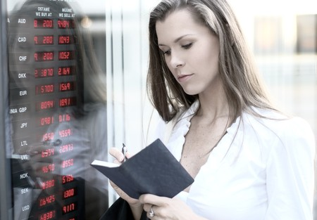 trader: A young businesswoman is checking the currency state