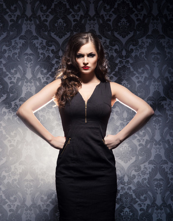 dominant woman: Young and emotional woman in fashion dress over glamour background