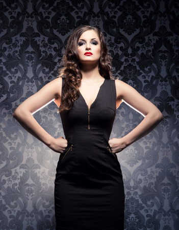 Young and emotional woman in fashion dress over glamour background