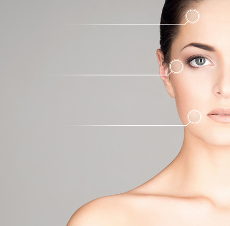 Close-up portrait of young, fresh and natural woman with the dotted arrows on her face Stockfoto