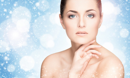 Portrait of healthy young woman over winter background