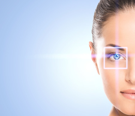 female eyes: Close-up portrait of young and beautiful woman with the virtual hologram on her eyes (laser medicine and security technology concept)