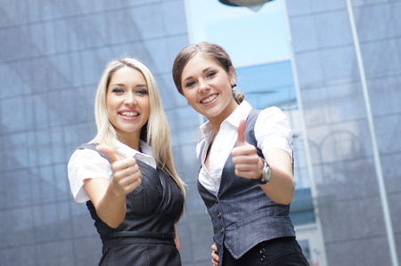 demonstrate: Two young attractive business women demonstrate the success Stock Photo