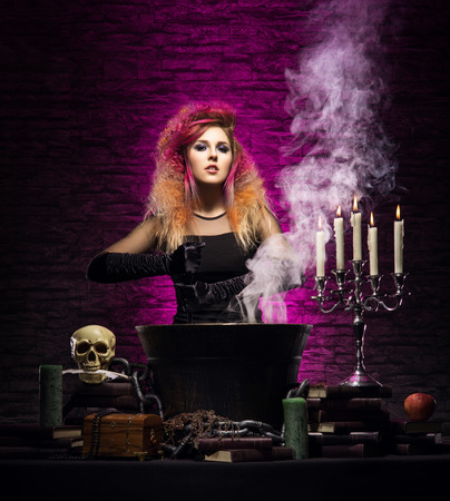dungeon: Young and beautiful witch in a dungeon. Halloween concept.