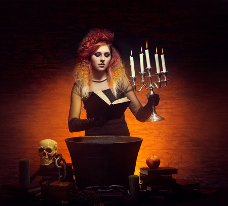 dungeon: Young and beautiful witch making a witchcraft in dungeon. Halloween concept.