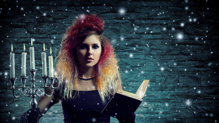 Beautiful witch making witchcraft over winter background photo