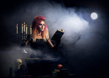 연기가 자욱한 배경 위에 마법을 아름다운 마녀. 할로윈 이미지.