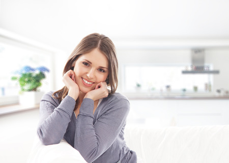girl alone: Beautiful and happy young woman sitting on the sofa over the kitchen background Stock Photo