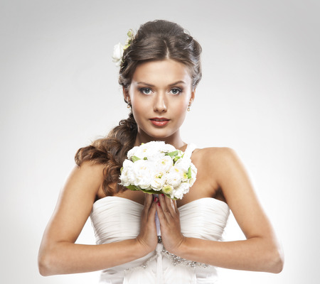 Mladý atraktivní nevěsta s kyticí bílých růží