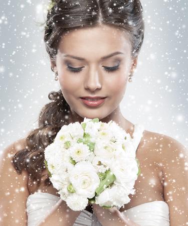fantasy makeup: Novia atractiva joven con el ramo de rosas blancas sobre fondo cubierto de nieve de Navidad