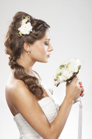 hair style: Young attractive bride with the bouquet of white roses Stock Photo