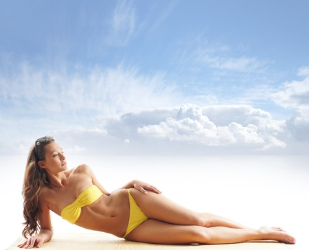 Young sexy brunette in yellow swimsuit