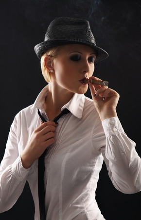 gangster background: Young attractive female gangster smoking cigar over dark background Stock Photo