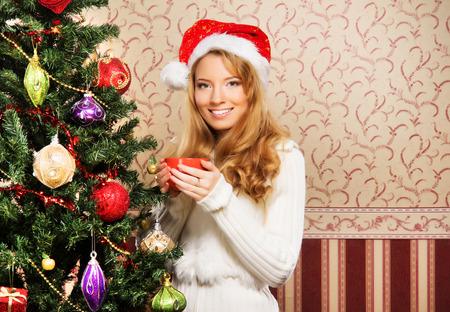 emot: Beautiful teenager girl decorating the Christmas tree Stock Photo