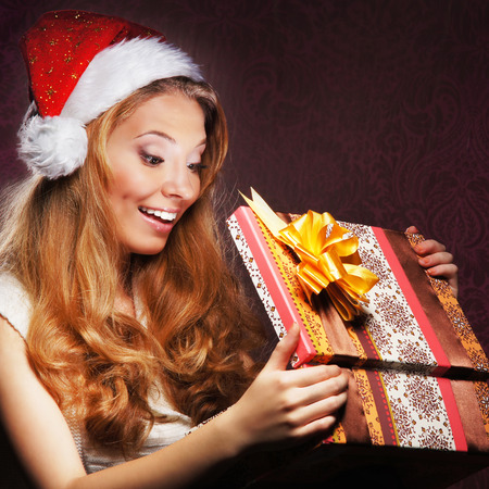 Young teenage girl opening the present photo