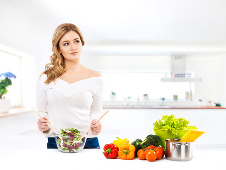 Young and beautiful housewife woman cooking in a kitchen 스톡 콘텐츠