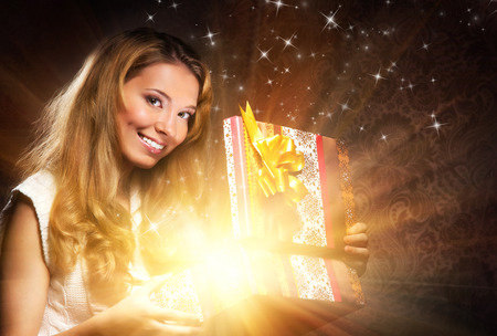 unwrapping: Young, happy and emotional teenage girl opening the magical Christmas present box