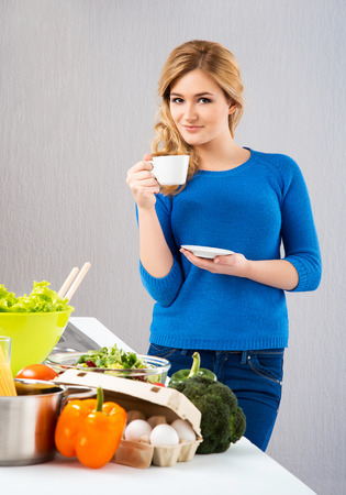 Young and beautiful housewife woman cooking in a kitchen photo