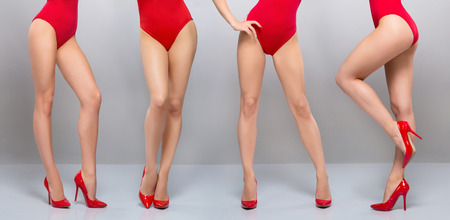Beautiful legs of young and sporty woman in red swimsuit over grey background Foto de archivo