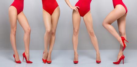 piernas sexys: Hermosas piernas de mujer joven y deportivo en traje de baño rojo sobre fondo gris