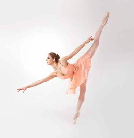 Young and beautiful ballerina dancing over white background photo