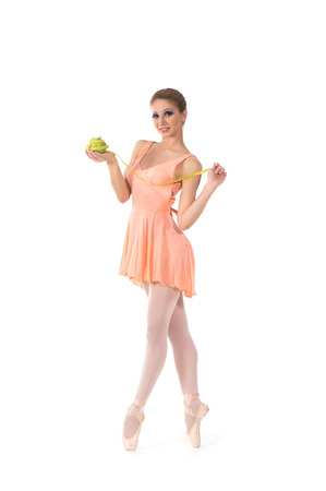 Young and beautiful ballerina dancing with a measuring tape and apple over white background photo