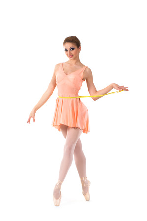 Young and beautiful ballerina dancing with a measuring tape over white background photo