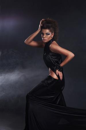 satanist: Woman in black long dress over dark background