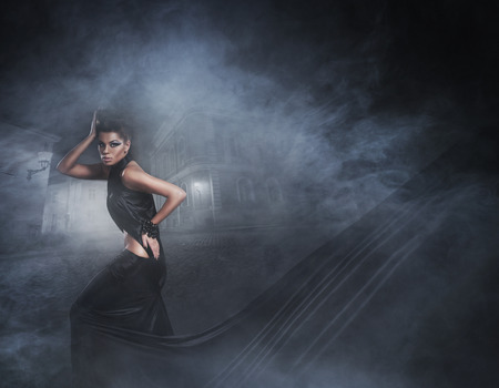 satanist: Halloween concept with the young sexy witch running down the street in a black long dress Stock Photo