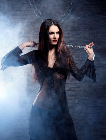 satanist: Halloween concept: young and sexy witch in the dungeon